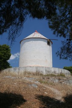 Below the renovated white windmill (milos), facing the islands of Dokos and Hydra, is the ancient nobleman's tomb.