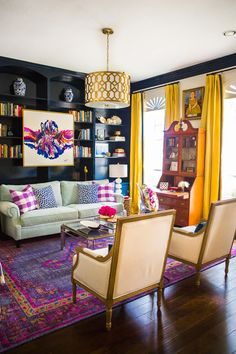 In this wildly colorful living room, @hisugarplum worked with designer @huntedinterior to create a glam, jewel-toned look while incorporating an antique secretary desk (a family heirloom), a traditional roll-arm sofa and Louis XVI-style chairs.