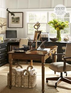 Pottery Barn home office farmhouse table as desk and wall storage pieces under windows in family room