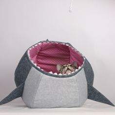 Hi we are The Cat Ball, LLC and we make a unique bed called the Cat Ball®. Here we've remade our design to be a shark- allowing you to watch your kitty get eaten alive by the most fascinating predator in your living room: a Great White Shark! Made with the same thick, compressible and cozy materials as the Cat Ball® cat bed, this shark also features the sharp teeth and strange, creepy eyes of a Great White Shark.