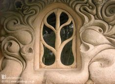 This stunningly beautiful window surrounded by swirls of cob looks out over the banks of a small stream in Somerset, England where the local dialect still has remnants of the Anglo-Saxon language. You can see more pictures of this home and read about building with cob at www.naturalhomes.org/goatlings.htm