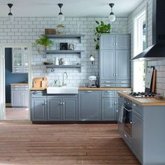 Blue, gray and warm wood with subway tiles.