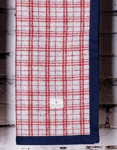 Gramercy Wool Blanket. Tartan plaid blanket is crafted from the finest wool and finished with contrasting navy blue trim.
