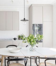 Cozinha escandinava toda branca e off-white, bem clean com pendente preto em cima da mesa de jantar.
