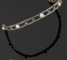 A diamond and button pearl bandeau, 1910. A simple lattice, with cicular diamonds at the crossing points and five button pearls as highlights.