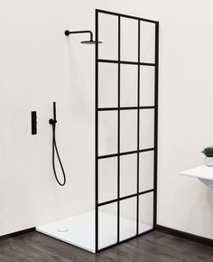 Grid shower panel inspired by Crittall windows. Shown with Nero hand held and overhead shower fittings. From Aston Matthews