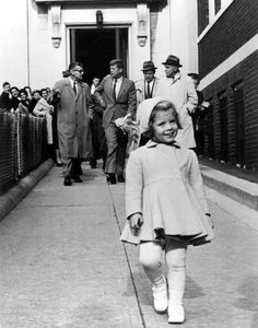 Caroline Kennedy walks ahead while her father, the most powerful man in the world, carries her doll. (1960)