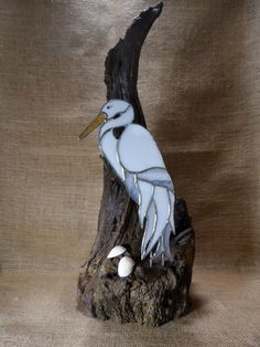 Stained glass Heron (Egret) on a very old Oak stump, with a couple of shells. At Jitter Beans in Mineral Wells, Texas.