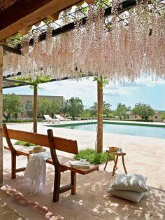 Pérgola    Bajo los racimos de glicina, junto a la piscina, un banco de herencia familiar y cojines, de Rialto Living.