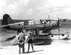 """warhistoryonline: """"OS2U Kingfisher at the edge of the seaplane ramp at NAS Pensacola, Florida, United States, early 1941. Note Consolidated P2Y flying boat laying off shore...."""