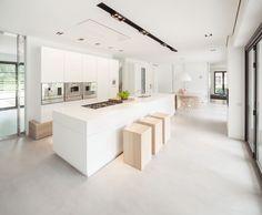 Villa in Huizen by De Brouwer Binnenwerk | HomeAdore Grijze gietvloer - witte keuken - warmte van hout