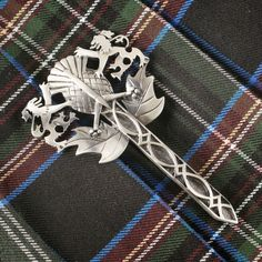 """Beautiful Scottish Kilt Pin. This pin masterly combines three of the most iconic symbols of Scotland – Rampant Lion, Thistle and Claymore Sword. Crafted of lead-free pewter with a sterling silver overlay. Attention getting and a bold look for kilts or jacket collars. 4""""L x 2 ¼""""W. Imported."""