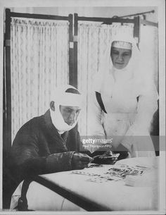 A wounded Belgian soldier with a British nurse undergoing convalescence during World War One, Great Britain, circa 1914-1918.