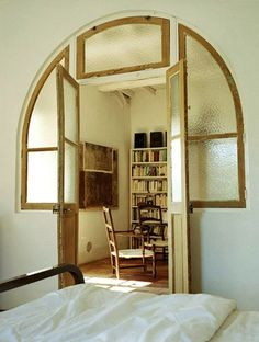 This is an excellent way to keep the light flowing from room to room, and to keep the appearance of an arch, but without having to get a specialty door & frame. A good idea all around, and very stylish too.