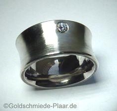 Ein leicht mattierter Silber-Ring mit Brillant. Der Ring ist nach außen gewölbt. Der eingelassene Brillant sitzt an der Aussenkante der Schiene.