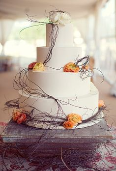 Brides.com: . A four-tiered wedding cake with peach and white roses and ranunculus and decorated with rustic branches, created by Creme de la Creme Cake Company.