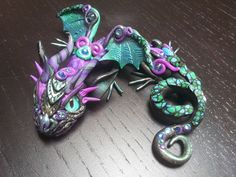 Baby dragon hand sculpted and with swarovsky details. Hand painted glass eyes.