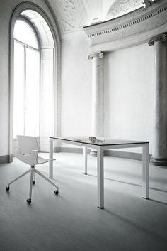 Taglio di luce per illuminare tavolo e sedia. L'ufficio è minimale e moderno. - Beam of light to illuminate a table and chair. The office is minimal and modern.
