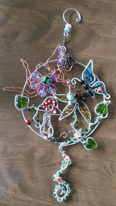 Wire wrapped beaded sun catcher with butterfly and flowers and ladybugs and garden fairy. Mushroom.