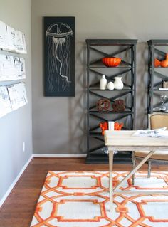 In this dining room, orange sets the shelving units and wood floors on fire through accessories and a patterned area rug.