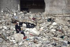 A Syrian woman sits on the ruins of her house, which was destroyed in an airstrike by government warplanes a few days earlier, killing 11 members of her family, in the neighborhood of Ansari, Aleppo, on February 6, 2013. (AP Photo/Abdullah al-Yassin)