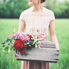 Wooden crate of flowers; lovely blouse and skirt, all in all it is nice to live in the country with a beautiful woman and beautiful flowers and be redeemed by a God of majesty who created it all.