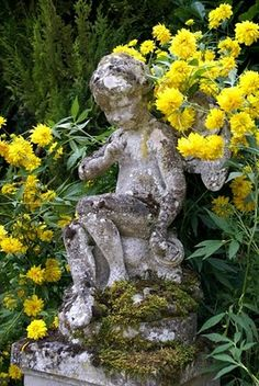 my french country home: Visiting our valley.  Vintage concrete garden cherub amount bright yellow flowers in a French garden bed.