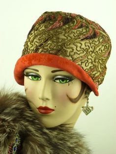 early 1920's America, ladies helmet cloche. It is made of gold silk with bouillon embroidery with red velvet trimming within the embroidered panels.  The brim is a turn back bright red velvet in traditional cloche style.  orange silk lining.