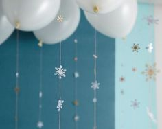 falling snowflake garlands - attach garlands to helium filled balloons. Could also do this with hearts or flowers or raindrops punched out of craft paper. Click through for the tutorial.