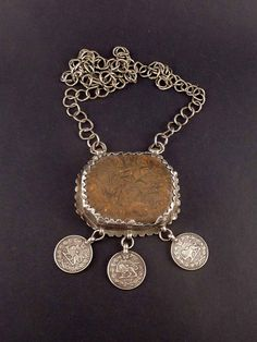 This is quite a big stone pendant, inside a silver frame and a handmade silver rings chain. There's also 3 iranian silver coins hanging from the pendant. It's an unusual necklace. The brown stone may have a protective meaning. This is and old piece of jewelry that have a nice worn patina.