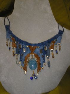 Blue fibers with brown accents woven to display the beautiful blue quartz oval stone hanging from the center. Various stones hang along the bottom