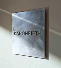 Placa de metal para exterior con letras estarcidas.