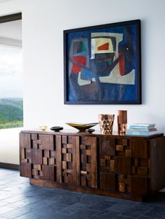 A Laubscher painting hangs above a Brutalist sideboard from Lane Furniture. The metal vases are by Tom Dixon; the bowls are Murano glass