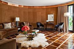 The screening room in this 1951 Hollywood Hills home is pure Hollywood Glam. The walls are swathed in suede and feature copper crown molding. Madeline Stuart designed the seating for the room, pairing it with a French bronze cocktail table from the 1970s.