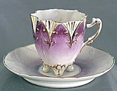 Vintage Violet & White Cup & Saucer: Tulip type flower cup. 8 violet pointed petals edged & embossed in a gold design. Between violet petals are white fan inserts decorated in gold on making the cup 16 sided. Cup has 4 feet & fancy handle. Saucer embossed & gold rim.
