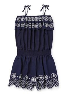 100% Viscose Playsuit. Woven, sleeveless playsuit with elasticated waistband and tie shoulder straps. Features layered frills at top and leg with embroidery. Relaxed fitting silhouette. Available in Navy.