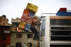 A porter loaded baskets used to carry vegetables and fruits on top of a bus near a vegetable market in Katmandu, Nepal, Thursday.  6/21/12