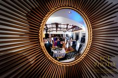 An imaginative shot of the wedding reception guests on the dancefloor seen reflected in the cool mirror during the party for the bride and groom following their wedding ceremony at Harbour Ridge Yacht and Country Club in Pt St Lucie Florida.