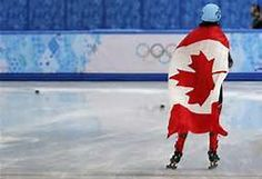Charles Hamelin of Canada wears his country's flag as he celebrates his victory in the men's 1,500 metres short track speed skating finals event at the Iceberg Skating Palace during the 2014 Sochi Winter Olympics February 10, 2014. REUTERS/Alexander Demianchuk.