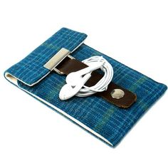 iPod & iPhone Pocket (by Mari Forssell) (2/4) - Lined with water resistant off-white canvas, comes with a rivet-reinforced brown leather strap with a snap closure, has a handy metal eyelet that's strategically placed for the earbud plug, includes a pocket for 2-3 credit cards.