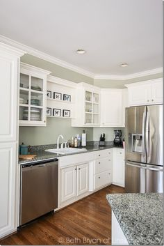 White kitchen with green granite counters and stainless steel