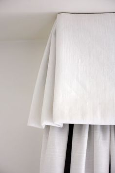 White linen box pleated valance with kick-pleat corners --