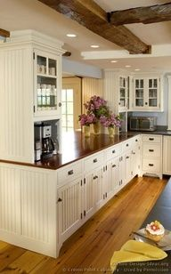 I love everything about this kitchen! Floors, dark brown counters, cream beadboard cabinets, coffee station with glass cupboards and mugs on display, oh and the beams on the ceiling. Dreamy!!