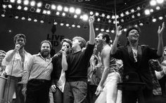 On July 13, Michael performed at Live Aid at Wembley Arena. Here he is (far left) alongsideconcert promoter Harvey Goldsmith, Bono of U2, Paul McCartney, concert organiser Bob Geldof and Freddie Mercury of Queen. During the concert,George joinrfElton John to perform Don't Let the Sun Go Down on Me.