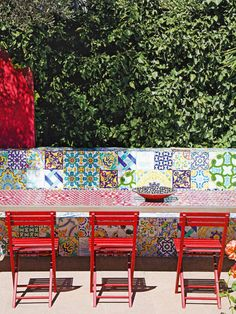 Mesa para área externa  com trampo geométrico e cadeiras vermelhas