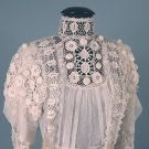 "IRISH CROCHET & NET DRESS, c. 1905  Unlined 1-piece, white cotton net w/ Irish crochet sleeves, bodice & deep hem flounce, exceptionally padded lace florals, B 38"", W 32"", front L 57"", back L 73"""