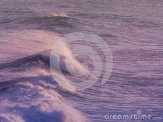 A view of purple and pink tinted ocean waves at sunset.