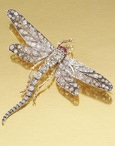 RUBY AND DIAMOND BROOCH, CIRCA 1900 | Designed as a dragonfly, its wings, thorax and tail set with circular-cut and cushion-shaped diamonds, its eyes embellished with cabochon rubies, detachable brooch fitting.