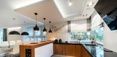 Modern kitchen interior design in black and white style, showign pundants, ambient lights, and recessed task lighting.