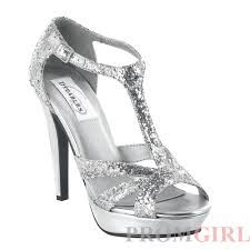 """Made in silver glitter material, this style t-strap platform sandal will match with almost any outfit. An adjustable buckle secures the ankle-strap allowing for stability when wearing this 4"""" heel. Gr"""